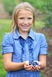 Blondes Mädchen mit dem neuen ausgewählten Blaubeere-Lächeln Lizenzfreie Stockfotos