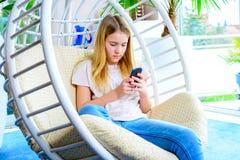 Blondes Mädchen mit dem Telefon, das im Stuhl sitzt Lizenzfreie Stockbilder