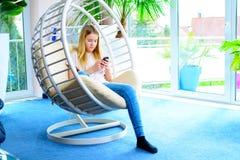 Blondes Mädchen mit dem Telefon, das im Stuhl sitzt Stockfotografie