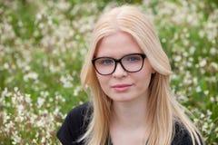 Blondes Mädchen mit den Gläsern umgeben durch Blumen Lizenzfreie Stockfotografie