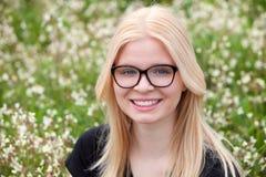 Blondes Mädchen mit den Gläsern umgeben durch Blumen Lizenzfreies Stockbild