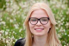 Blondes Mädchen mit den Gläsern umgeben durch Blumen Stockfoto