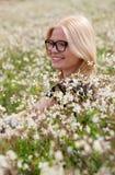 Blondes Mädchen mit den Gläsern umgeben durch Blumen Stockbilder