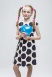 Blondes Mädchen mit den Zöpfen, die in der Polka Dot Dress Against White aufwerfen Lizenzfreie Stockbilder