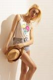 Blondes Mädchen mit Denimkurzschlüssen und Hut in den Händen Stockfotos