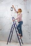 Blondes Mädchen mit der beleuchteten Laterne, die auf Stehleiter steht Stockfotografie