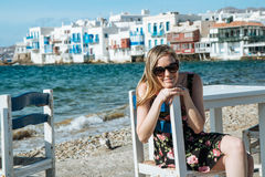 Blondes Mädchen mit der Sonnenbrille, die auf einem Stuhl am Strand sitzt Stockfotos