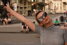 Blondes Mädchen mit der Sonnenbrille, die frei glaubt Lizenzfreie Stockfotos