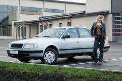 Blondes Mädchen mit einem Auto am leeren Parkenplatz. Stockfoto