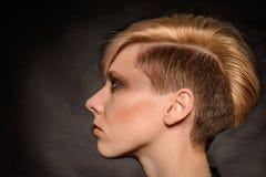 Blondes Mädchen mit einem kurzen stilvollen Haarschnitt Stockfotos