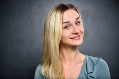 Blondes Mädchen mit einem schlauen Lächeln auf einem grauen Wandhintergrund Lizenzfreies Stockbild