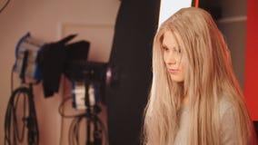 Blondes Mädchen mit Fachmann bilden die Aufstellung im Studio für Fotografen Stockfotos