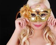 Blondes Mädchen mit Goldkarnevalsmaske über schwarzem Hintergrund. Maskerade Stockfotografie