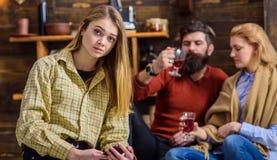 Blondes Mädchen mit großen Augen im gelben Weinlesehemd, das im Wohnzimmer des hölzernen Häuschens der Landschaft sitzt Bärtiger  Lizenzfreies Stockbild