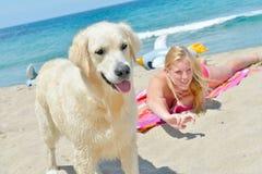 Blondes Mädchen mit Hund auf dem Strand Stockfoto