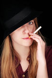 Blondes Mädchen mit Hut und eine Zigarette, die Kamera betrachtet Lizenzfreie Stockfotografie