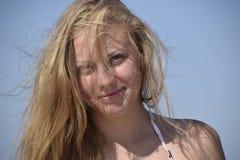 Blondes Mädchen mit ihrem Haar auf Hintergrund des blauen Himmels Schöne junge Frau Lizenzfreie Stockfotos