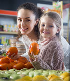 Blondes Mädchen mit kaufenden Mandarinen der Mutter im Shop Stockfotos