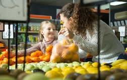 Blondes Mädchen mit kaufenden Mandarinen der Mutter im Shop Stockfotografie