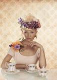 Blondes Mädchen mit klassischem Teesatz und -hand darunter Stockbilder