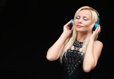 Blondes Mädchen mit Kopfhörern die Musik über Schwarzem genießend Lizenzfreies Stockbild
