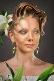 Blondes Mädchen mit Make-up und schönes Haar auf grauem Hintergrund Lizenzfreie Stockfotografie