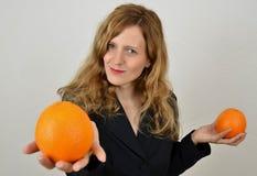 Blondes Mädchen mit Orangen, im Büroanzug Stockfotos