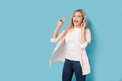 Blondes Mädchen mit orthodontischen Klammern hört Musik Lizenzfreie Stockfotografie