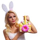 Blondes Mädchen mit Ostern-Korb lokalisiert Stockfotografie