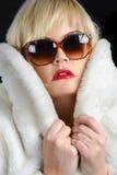 Blondes Mädchen mit Pelzmantel und Sonnenbrillen Stockbild
