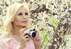 Blondes Mädchen mit Retro- Kamera über Kirschblüte. Schöne junge Frau Stockfoto