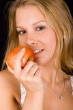Blondes Mädchen mit rotem Apfel Lizenzfreies Stockfoto