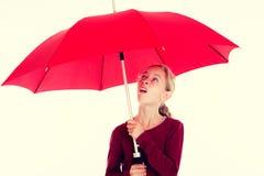 Blondes Mädchen mit rotem Regenschirm Stockfotos