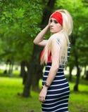 Blondes Mädchen mit rotem Schal und gestreiftem Kleid Stockfotos