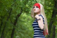 Blondes Mädchen mit rotem Schal und gestreiftem Kleid im Wald Stockbild
