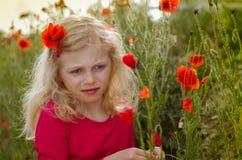 Blondes Mädchen mit roten Mohnblumenblumen Stockfoto