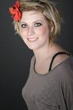 Blondes Mädchen mit roter Blume in ihrem Haar Lizenzfreies Stockfoto