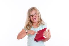 Blondes Mädchen mit runden Gläsern zeigend auf rotes Buch Lizenzfreies Stockfoto