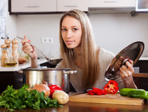 Blondes Mädchen mit Schöpflöffel Suppe kochend Stockbild