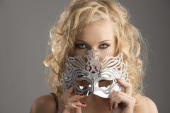 Blondes Mädchen mit silberner Schablone schaut innen zum Objektiv Lizenzfreies Stockbild