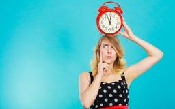 Blondes Mädchen mit Wecker auf Blau Lizenzfreies Stockfoto