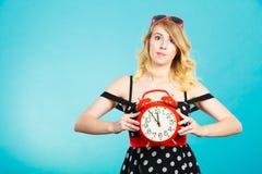 Blondes Mädchen mit Wecker auf Blau Stockfoto