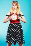 Blondes Mädchen mit Wecker auf Blau Lizenzfreie Stockbilder