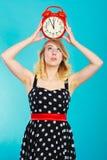 Blondes Mädchen mit Wecker auf Blau Lizenzfreies Stockbild