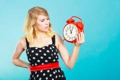 Blondes Mädchen mit Wecker auf Blau Stockfotografie