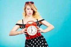 Blondes Mädchen mit Wecker auf Blau Stockfotos