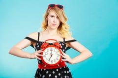 Blondes Mädchen mit Wecker auf Blau Lizenzfreie Stockfotografie