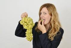 Blondes Mädchen mit Weintraube kleidete im Büroanzug an Lizenzfreie Stockfotos