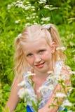 Blondes Mädchen mit zwei Endstücken, sitzend im grünen Gras mit Fluss Lizenzfreie Stockfotos