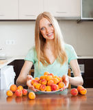 Blondes Mädchen nahe Haufen von Aprikosen Stockfotografie